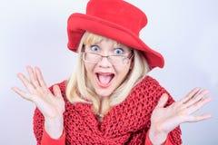 一名美丽的正面妇女的特写镜头画象有惊人的长的头发白肤金发的明亮的红色帽子和被编织的围巾的 图库摄影