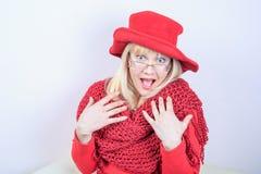 一名美丽的正面妇女的特写镜头画象有惊人的长的头发白肤金发的明亮的红色帽子和被编织的围巾的 库存照片
