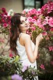 一名美丽的深色的妇女的画象桃红色礼服的和五颜六色在杜娟花庭院里组成户外 免版税库存照片