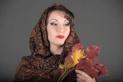 一名美丽的深色头发的妇女的画象有一条围巾的在她的头和秋叶 库存照片
