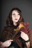 一名美丽的深色头发的妇女的画象有一条围巾的在她的头和秋叶 免版税库存照片