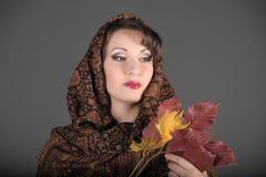一名美丽的深色头发的妇女的画象有一条围巾的在她的头和秋叶 图库摄影
