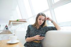 一名美丽的白肤金发的妇女在与一个时髦的设计的一个精美咖啡馆使用一个电话 库存照片