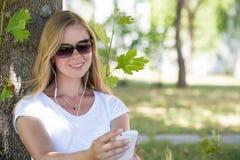 一名美丽的白肤金发的妇女在公园和冲浪  免版税图库摄影