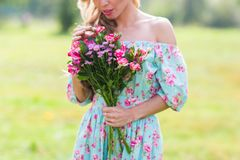 一名美丽的白肤金发的妇女的特写镜头室外画象 一个领域的可爱的愉快的女孩与花花束  免版税库存照片