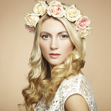 一名美丽的白肤金发的妇女的纵向有花的在她的头发 免版税库存照片