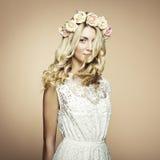 一名美丽的白肤金发的妇女的纵向有花的在她的头发 库存图片