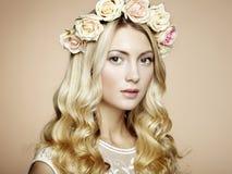 一名美丽的白肤金发的妇女的纵向有花的在她的头发 库存照片