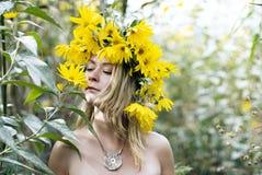 一名美丽的白肤金发的妇女的纵向有花的 免版税库存照片
