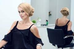 一名美丽的白肤金发的妇女的画象美发师的 免版税库存照片