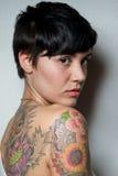 一名美丽的短头发深色的妇女的背面图有纹身花刺的 免版税库存照片