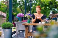 一名美丽的聪明的妇女的画象有明亮的红色头发的 一件黑礼服的时髦的女孩,吃在土地的冰淇凌 库存照片