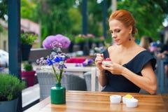 一名美丽的聪明的妇女的画象有明亮的红色头发的 一件黑礼服的时髦的女孩,吃在土地的冰淇凌 免版税库存照片