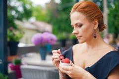 一名美丽的聪明的妇女的画象有明亮的红色头发的 一件黑礼服的时髦的女孩,吃在土地的冰淇凌 免版税图库摄影