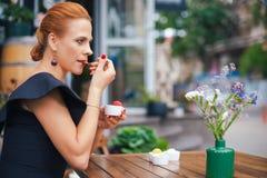 一名美丽的聪明的妇女的画象有明亮的红色头发的 一件黑礼服的时髦的女孩,吃在土地的冰淇凌 库存图片