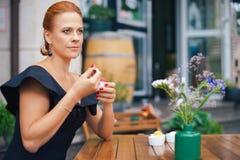 一名美丽的聪明的妇女的画象有明亮的红色头发的 一件黑礼服的时髦的女孩,吃在土地的冰淇凌 免版税库存图片