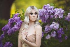 一名美丽的肉欲的年轻白肤金发的妇女的画象在春天 开花的日庭院可能反弹晴朗 金礼服的女孩 免版税库存照片
