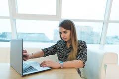 一名美丽的自由职业者的妇女在她的膝上型计算机的一个时髦的咖啡馆工作 免版税图库摄影