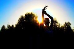 一名美丽的跳舞妇女和手的剪影在日落在树背景  免版税库存图片