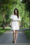 一名美丽的年轻白种人妇女的全长画象白色礼服的有开放肩膀、干净的皮肤、长的头发和偶然mak的 库存照片