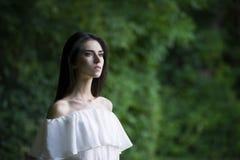 一名美丽的年轻白种人妇女的画象白色礼服的有开放肩膀、干净的皮肤、长的头发和偶然构成的 免版税库存图片