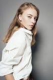 一名美丽的年轻白肤金发的妇女的画象一件白色衬衣的在灰色背景的演播室 免版税库存图片