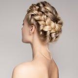 一名美丽的年轻白肤金发的妇女的画象有辫子冠头发的 免版税图库摄影