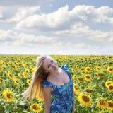 一名美丽的年轻白肤金发的妇女的画象蓝色礼服的在ba 免版税库存图片