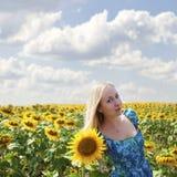 一名美丽的年轻白肤金发的妇女的画象蓝色礼服的在ba 免版税图库摄影