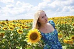 一名美丽的年轻白肤金发的妇女的画象蓝色礼服的在ba 图库摄影