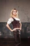 一名美丽的steampunk妇女的画象短装衣裤的与背心,在难看的东西背景 图库摄影