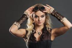 一名美丽的steampunk妇女的画象飞行员玻璃的在灰色背景 查看照相机 库存图片