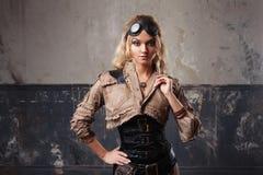 一名美丽的steampunk妇女的画象飞行员玻璃的在难看的东西背景 免版税库存照片