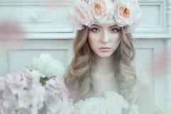 一名美丽,甜妇女的画象有玫瑰的在卷发 在花附近 库存照片