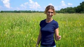 一名美好的苗条妇女立场和微笑在草甸,指法新鲜的草的小尖峰在一清楚的好日子 影视素材