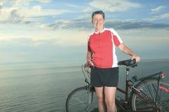 一名老人和一名妇女自行车的在日落 库存图片