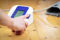 一名老前辈/妇女由电准备测量的血压 免版税库存照片