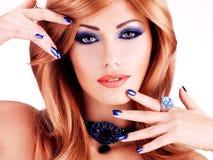 一名肉欲的美丽的妇女的特写镜头面孔有蓝色钉子的 免版税库存照片