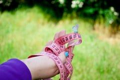一名肥胖妇女在她的手上拿着桃红色颜色一卷测量的磁带,对此坐一只蓝色蝴蝶 免版税库存照片