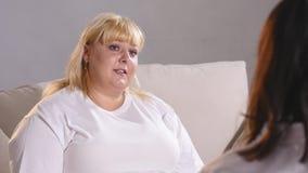 一名肥胖妇女抱怨给营养师她的图 肥胖妇女哭泣 免版税库存图片