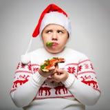 一名肥胖妇女的画象用一个大三明治在她的手上 她戴一个欢乐圣诞节毛线衣和圣诞老人帽子 免版税库存照片