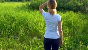 一名苗条妇女在有桃红色三叶草花的一个绿色草甸赤足走在一个晴朗的夏日 影视素材