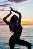 一名苗条妇女的剪影,谁做在前面的瑜伽 库存照片