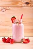 一名草莓圆滑的人的特写镜头在金属螺盖玻璃瓶的 在木背景的可口酸奶 与红色秸杆的一个液体点心 免版税库存照片