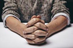 一名资深妇女的祈祷的手 免版税库存图片