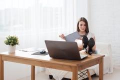 一名轻松的年轻女实业家的画象与腿坐书桌在办公室 免版税库存图片