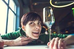 一名醉酒的妇女坐在桌上 免版税库存图片