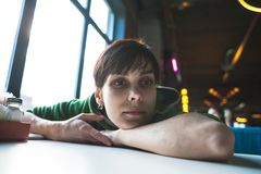 一名醉酒的妇女坐在桌上 免版税库存照片