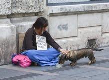 一名饥饿的妇女乞求在街道的施舍 库存图片