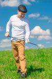 一名高尔夫球运动员的画象有一家高尔夫俱乐部的在一个晴天 免版税库存照片